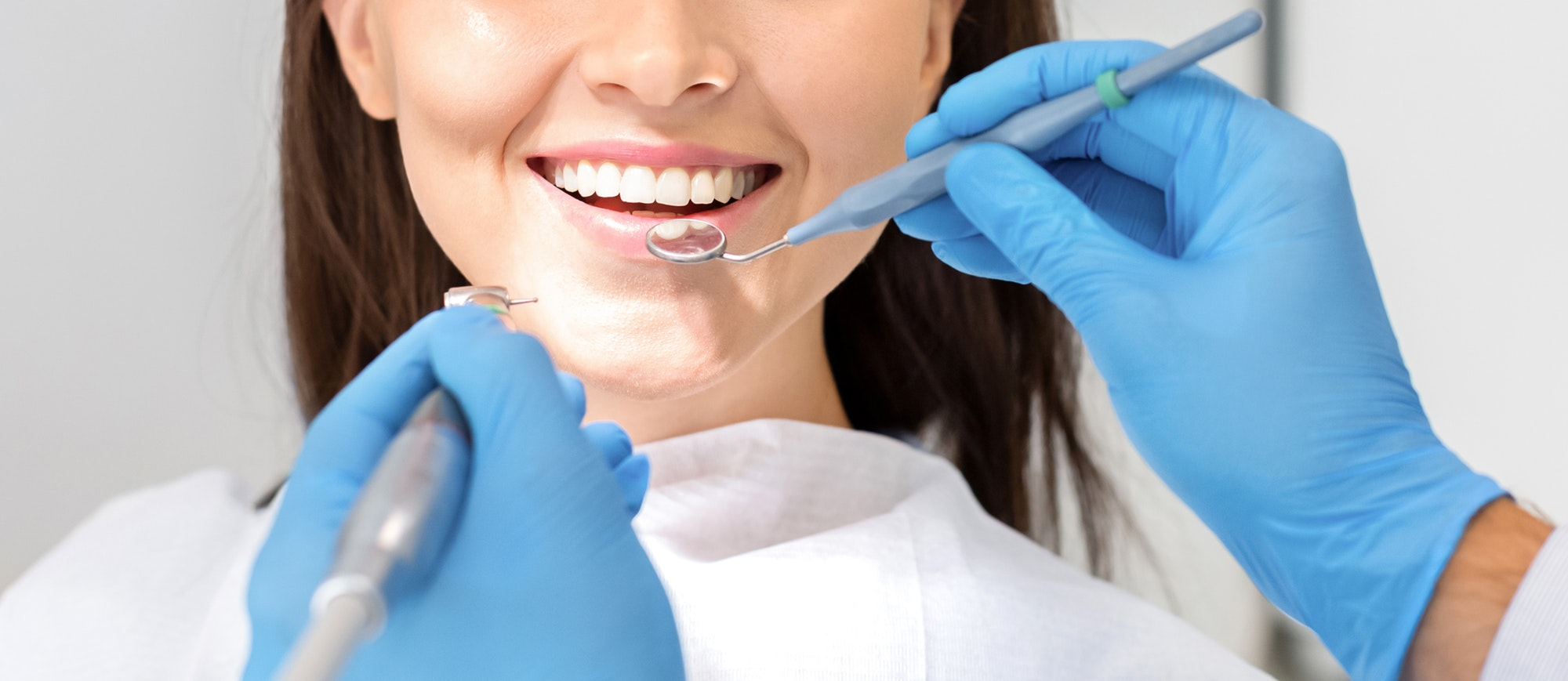 Cropped photo of woman mouth under treatment at dental clinic
